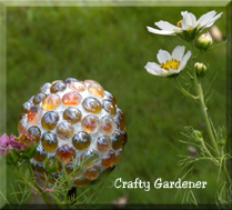 a mini gazing ball made from a rubber ball and flat sided marbles/gems at craftygardener.ca